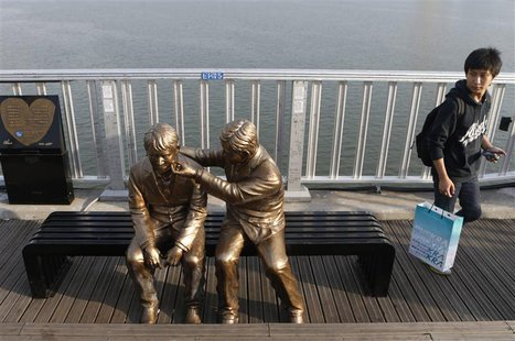 A man walks past a statue of a person comforting another on the Mapo Bridge, one of 25 bridges over the Han River, in central Seoul Septembe