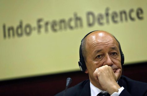 French Defence Minister Jean-Yves Le Drian listens to a reporter's question before addressing a gathering at the Institute for Defence Studi