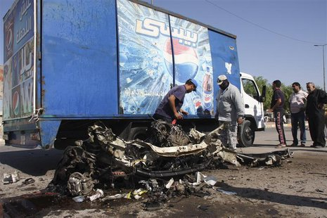 Residents inspect the mangled remains of a vehicle at the site of a car bomb attack in Baghdad's Sadr City, September 30, 2013. REUTERS/Wiss