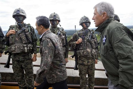 U.S. Secretary of Defense Chuck Hagel (R) walks past South Korean soldiers with South Korea's Defence Minister Kim Kwan-jin (2nd L) during a