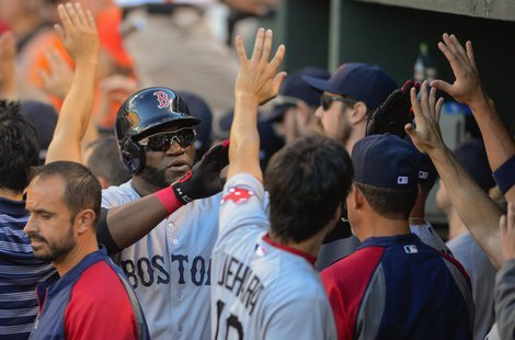 Boston Red Sox designated hitter David Ortiz is greeted by teammates after scoring in the ninth inning against Baltimore Orioles relief pitc