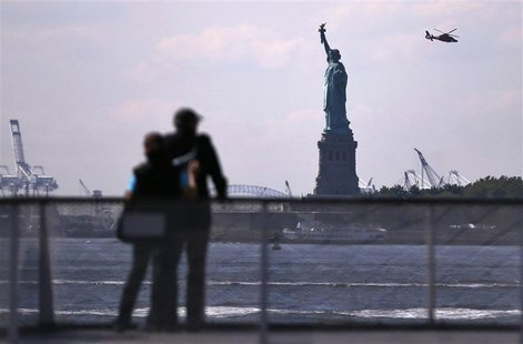 Tourists pause to view the Statue of Liberty from a Liberty Island ferry boat at Battery Park in New York, September 30, 2013. REUTERS/Mike