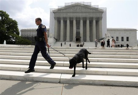 A policeman and his bomb sniffing dog walk in front of the Supreme Court in Washington, April 17, 2013. REUTERS/Larry Downing