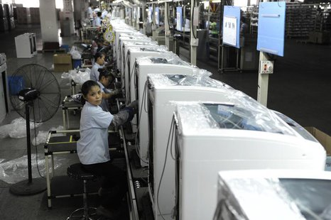 Employees assemble washing machines on the production line inside a factory of Hefei Rongshida Sanyo Electric in Hefei, Anhui province Augus
