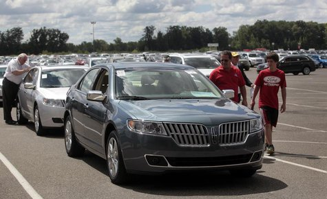 Auto dealership owners take a look at vehicles being auctioned off during an auto auction at Manheim Detroit Auto Auction in Carleton, Michi
