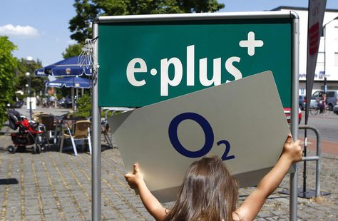 A young girl holds up the logo of O2 Deutschland, the German daughter of Spain's Telefonica, close to the E-Plus logo in front of an E-Plus