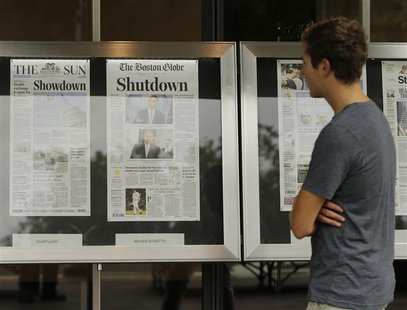 A man reads morning newspapers from around the U.S. at the Newseum in Washington October 1, 2013. REUTERS/Gary Cameron