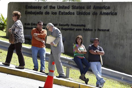 Pedestrians walk past a wall outside the U.S. embassy in Caracas October 1, 2013. REUTERS/Carlos Garcia Rawlins