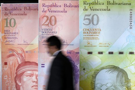 A man walks past big samples of Venezuelan bank notes at the Central Bank headquarters in Caracas August 22, 2013. REUTERS/Carlos Garcia Raw