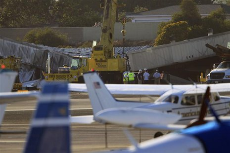 Workers prepare to use cranes to extract a twin-engine Cessna Citation 525A aircraft from inside a collapsed hangar which it slammed into, b