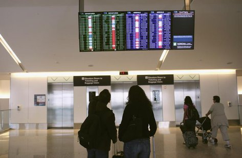 Airline passengers look at a flight status board at San Francisco International Airport in San Francisco, California April 22, 2013. REUTERS
