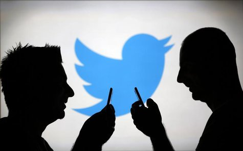 Men are silhouetted against a video screen with a Twitter logo as he poses with a Samsung S4 smartphone in this photo illustration taken in