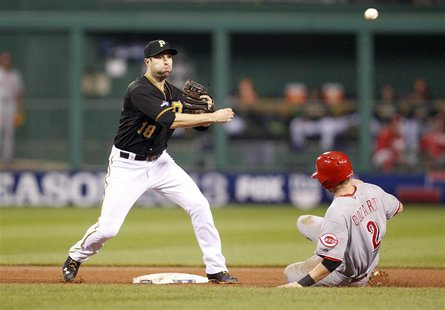 Oct 1, 2013; Pittsburgh, PA, USA; Pittsburgh Pirates second baseman Neil Walker (18) turns a double play over Cincinnati Reds shortstop Zack