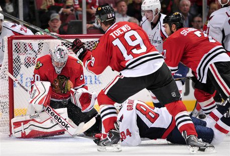 Oct 1, 2013; Chicago, IL, USA; Chicago Blackhawks goalie Corey Crawford (50) makes a save in front of center Jonathan Toews (19) and Washing