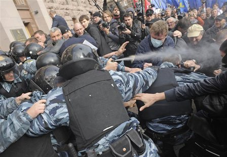 Activists of Ukrainian opposition parties clash with riot police as they attempt to get into the mayoral office during a rally against the K
