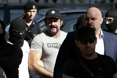 Extreme-right Golden Dawn party lawmaker Yannis Lagos (C) is escorted by anti-terrorism police officers after he was ordered to be kept in d