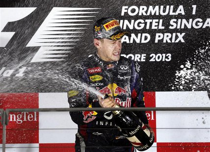 Red Bull Formula One driver Sebastian Vettel of Germany sprays champagne on the podium after winning the Singapore F1 Grand Prix at the Mari