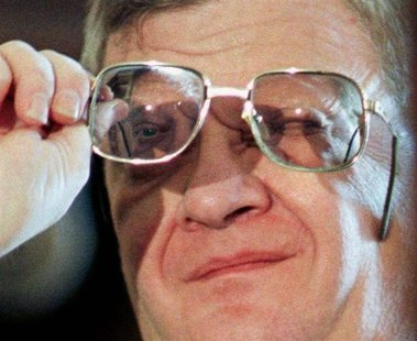 Novelist Tom Clancy checks his glasses in this file photo.
