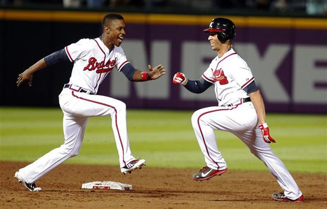 Atlanta Braves Andrelton Simmons (R) is chased by teammate B.J. Upton in celebration after Simmons hit a single knocking in the winning run