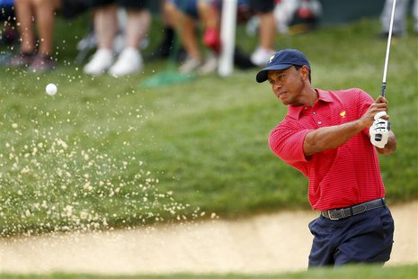 U.S. Team player Tiger Woods hits out of a bunker on the 12th hole during the second practice round for the 2013 Presidents Cup golf tournam
