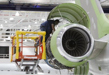 A worker looks at an engine on a Bombardier Global 5000 jet as its being assembled at the Bombardier aircraft manufacturing facility in Toro