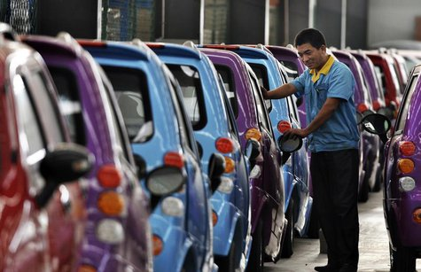 An employee checks newly-assembled electric cars to be exported to South America at an electric vehicle factory in Zouping county, Shandong