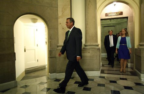U.S. House Speaker John Boehner (L) departs his office with his staff to go to the House floor for a series of votes on partial budget measu