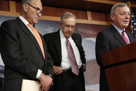 U.S. Senate Majority Leader Harry Reid (D-NV) (C) hitches up his belt during a news conference with Senator Charles Schumer (D-NY) (L) and S