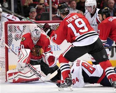 Chicago Blackhawks goaltender Corey Crawford stops a shot in front of Washington's Mikhail Grabovski (84) and Chicago's Jonathan Toews (19) during the Blackhawks' 6-4 win over the Capitals at Chicago's United Center on Oct. 1, 2013. (Reuters)