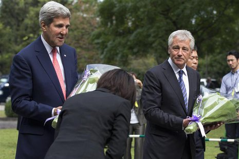 A woman bows to U.S. Secretary of State John Kerry (L) and U.S. Secretary of Defense Chuck Hagel as they participate in a wreath- laying cer