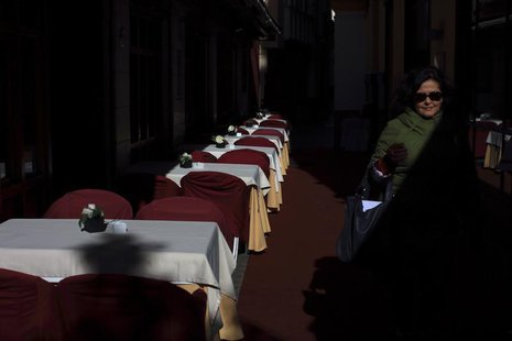 A woman walks past an empty restaurant in the Andalusian capital of Seville January 23, 2013. REUTERS/Marcelo del Pozo