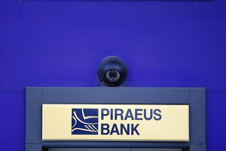 A surveillance camera is seen over the logo of Piraeus Bank on an ATM machine outside one of its branches in Bucharest April 18, 2013. REUTE