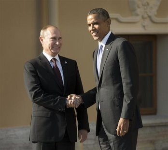 U.S. President Barack Obama (R) and Russia's President Vladimir Putin shake hands during arrivals for the G20 summit at the Konstantin Palac