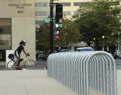 A lone cyclist waits for a traffic signal near empty bicycle racks in the Federal Center Plaza area during day three of the U.S. government