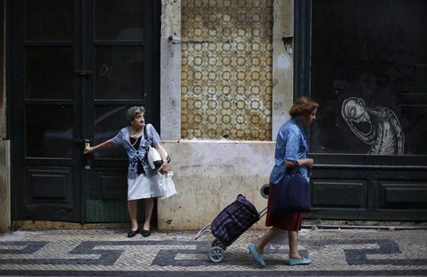 A woman pulls a shopping bag as another waits for a bus in downtown Lisbon July 11, 2013. REUTERS/Rafael Marchante