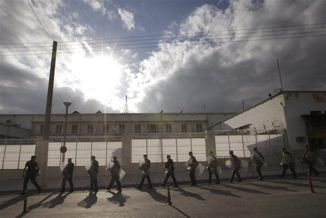 Riot policemen walk outside the Korydallos prison in Athens October 3, 2013. REUTERS/John Kolesidis