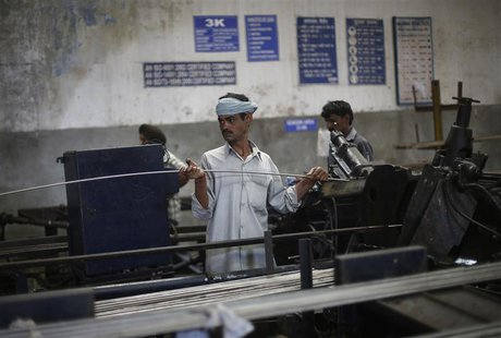 An employee holds a steel rod as he works on the production line inside Hallmark steel factory in Bhiwadi in the desert Indian state of Raja