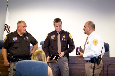 Deputy Todd Johnson awarded a purple heart by Sheriff Sam Wollin and Chief Deputy Terry Fahrenkrug.  Photo: Adams Co. Sheriff's Department