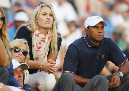 U.S. golfer Tiger Woods and girlfriend Lindsey Vonn sit with teammate Phil Mickelson and Phil's wife Amy (L) as they watch play during the o