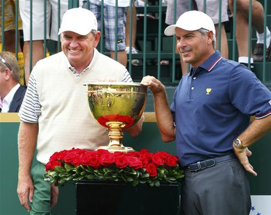 International team captain Nick Price (L) poses next to the Presidents Cup with U.S. team captain Fred Couples before first round play begin