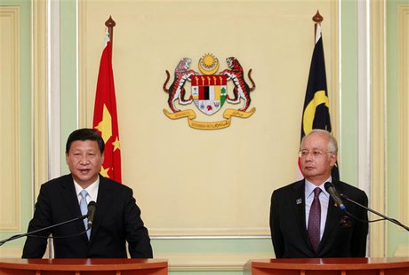 China's President Xi Jinping (L) speaks next to Malaysia's Prime Minister Najib Razak during a joint news conference at Najib's office in Pu