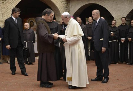 Pope Francis signs a book as he arrives at the San Damian monastery during his pastoral visit in Assisi October 4, 2013. REUTERS/Gian Matteo