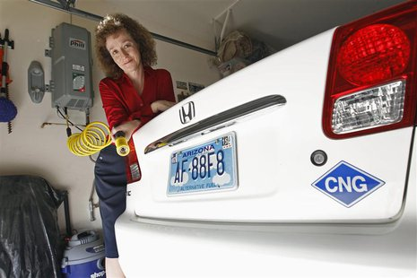 Connie Jones with her 2003 natural gas powered Honda Civic and natural gas home refueling station located on the garage wall of her home in