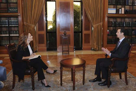 Syria's President Bashar al-Assad (R) speaks during an interview with Italian television station RaiNews24 in Damascus in this handout photo