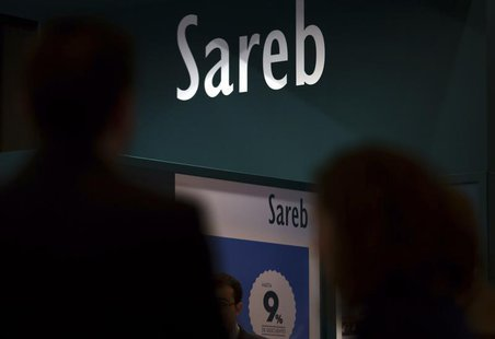 People walks past the stand of Spain's bad bank Sareb during a real estate fair in Madrid May 30, 2013. REUTERS/Sergio Perez