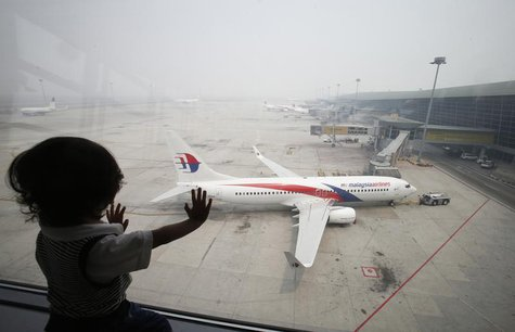 A boy looks out a window overlooking the haze-covered Kuala Lumpur International Airport in Sepang, outside Kuala Lumpur June 24, 2013. REUT