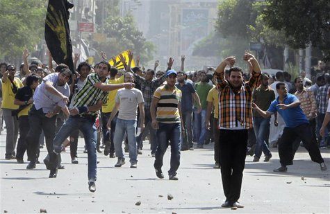 Supporters of deposed President Mohamed Mursi and the Muslim Brotherhood clash with anti-Mursi protesters during a march in Shubra street in