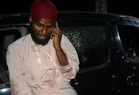 Salim Aboud talks on his phone after he survived the shooting at their vehicle in which Sheikh Ibrahim Ismael and three others were killed n