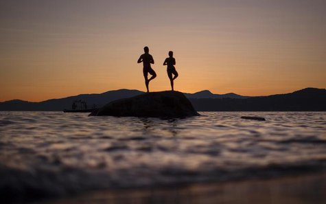A couple stand on a rock facing the sunset along the shores of English Bay in Vancouver, British Columbia July 23, 2013. REUTERS/Andy Clark