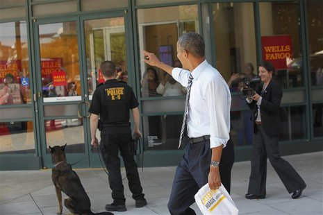 U.S. President Barack Obama waves at people in a bank vestibule after he and Vice President Joe Biden (not pictured) bought lunch at a sandw